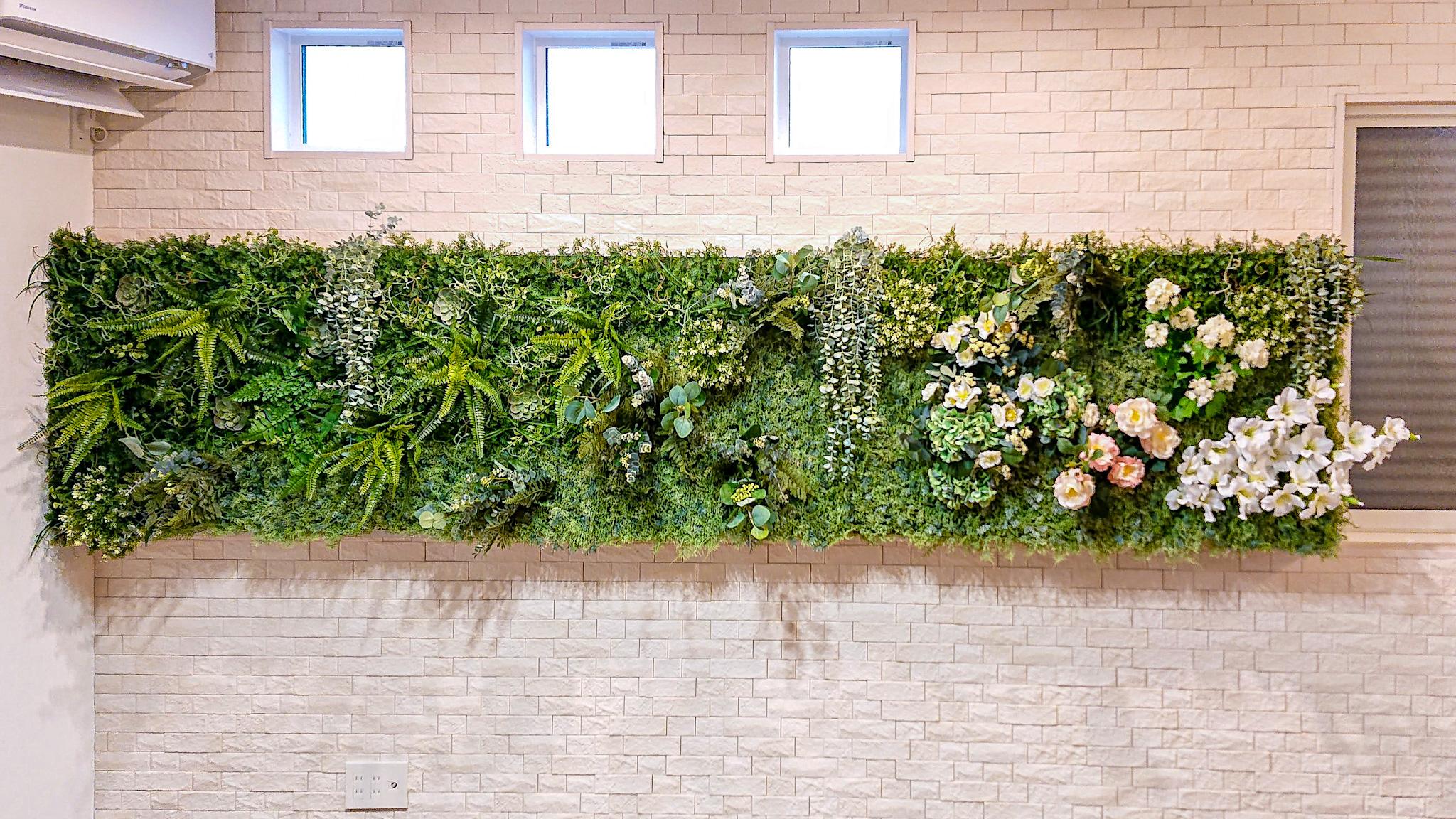 壁に直接土台を作り、フェイクグリーンで飾りました。土台の上下には間接照明を設置。装飾されたグリーンがより映えます。